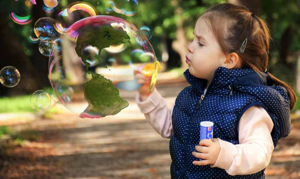 child blowing bubble earth